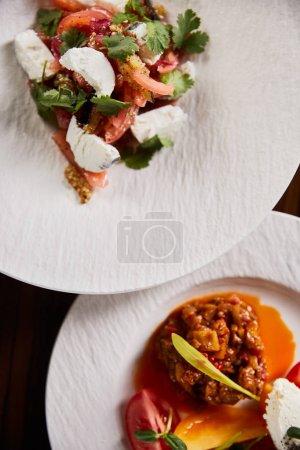 Photo pour Top vue sur le délicieux plat de restaurant avec aubergines caviar et tomates et salade sur table en bois - image libre de droit
