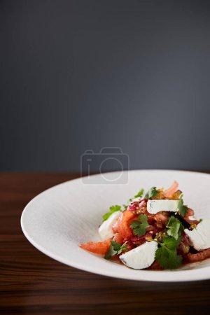 Photo pour Délicieuse salade de restaurant avec fromage servi en assiette blanche sur table en bois sur fond noir - image libre de droit
