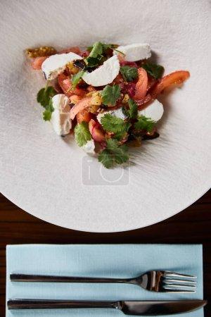 Photo pour Top vue sur une délicieuse salade de restaurant avec fromage servi en assiette blanche sur une table en bois avec couverts - image libre de droit