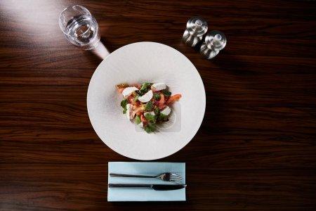 Photo pour Top vue sur une délicieuse salade de restaurant avec fromage servi en assiette blanche sur une table en bois avec de l'eau, de la coutellerie et des shakers de sel et poivre - image libre de droit