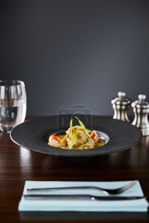 Photo for Selective focus of delicious restaurant soup with shrimps in black plate served on napkin with cutlery and water on black background - Royalty Free Image