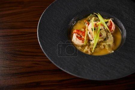 Photo pour Vue de près d'une délicieuse soupe de restaurant avec crevettes en assiette noire sur table en bois - image libre de droit