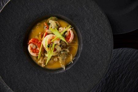 Photo pour Top view of delicious restaurant soup with shrimps in black plate. - image libre de droit