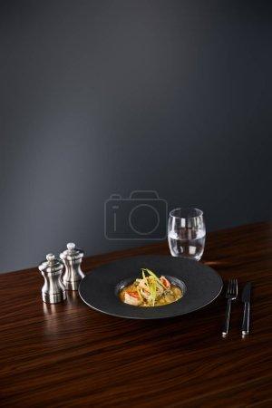 Photo pour Délicieuse soupe au restaurant avec crevettes en assiette noire servie sur serviette avec coutellerie et eau sur fond noir - image libre de droit
