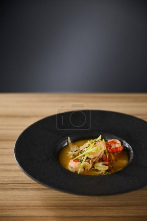 Photo pour Délicieuse soupe de restaurant avec crevettes en assiette noire sur table en bois sur fond noir - image libre de droit
