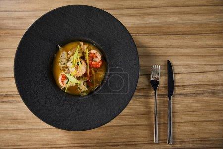 Photo pour Top vue de la délicieuse soupe de restaurant avec crevettes en assiette noire sur table en bois avec couverts. - image libre de droit