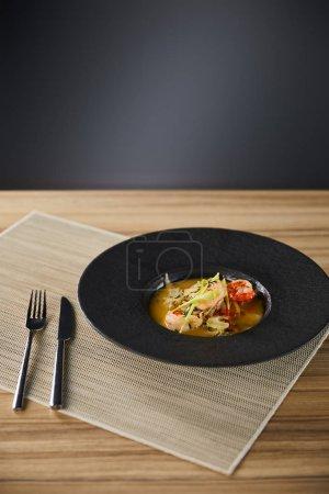 Photo pour Délicieuse soupe au restaurant avec crevettes dans une assiette noire servie sur serviette avec coutellerie - image libre de droit