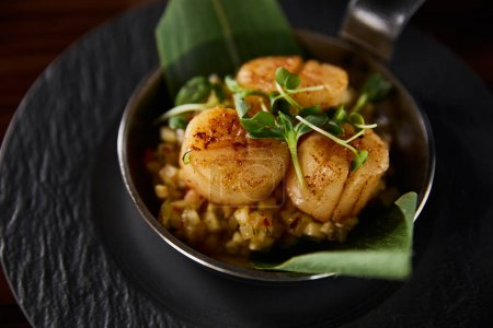 Photo for Delicious grilled scallops with green leaves and microgreens - Royalty Free Image