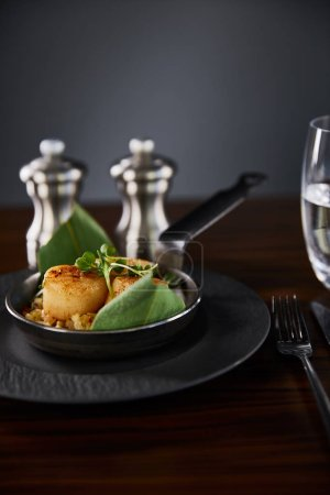 selective focus of delicious grilled scallops with green leaves and microgreens near cutlery, water and pepper, salt shakers