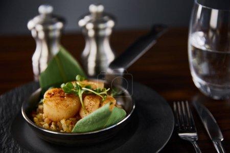 Photo pour Foyer sélectif de pétoncles grillés délicieux avec des feuilles vertes et microgreens près de couverts, eau et poivre, salières - image libre de droit