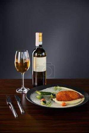 Photo pour Délicieux poulet kiev et purée de pommes de terre servis en assiette près de la coutellerie et vin blanc sur fond noir - image libre de droit