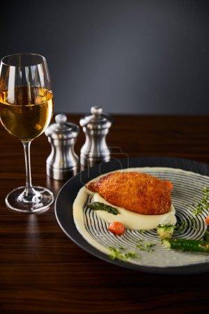 Photo pour Délicieux poulet kiev et purée de pommes de terre servis en assiette près du vin blanc sur fond noir - image libre de droit