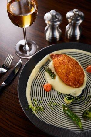 Photo pour Délicieux poulet kiev et purée de pommes de terre servis en assiette près de la coutellerie et du vin blanc - image libre de droit