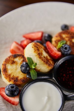 Photo for Close up view of traditional Ukrainian dish syrniki with strawberry, blueberry served with jam and sour cream - Royalty Free Image