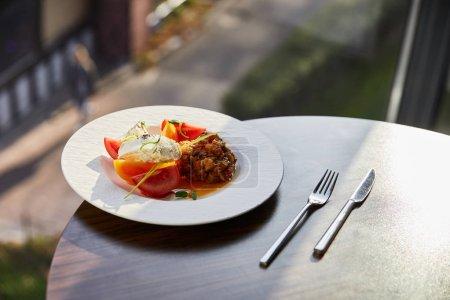 Photo pour Délicieux caviar d'aubergines avec tomates et beurre servi au restaurant sur table en bois avec couverts au soleil - image libre de droit