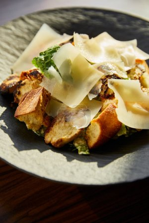 Photo for Close up view of tasty Caesar salad with Parmesan slices served on plate in sunlight - Royalty Free Image