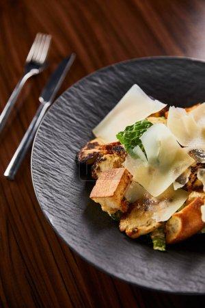 Photo pour Salade César avec tranches de Parmesan servies sur assiette avec couverts sur table en bois. - image libre de droit