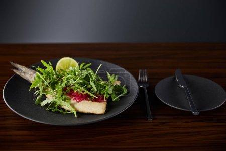 Photo pour Steak de poisson savoureux avec chaux et arugula sur table en bois près de la coutellerie sur fond noir - image libre de droit