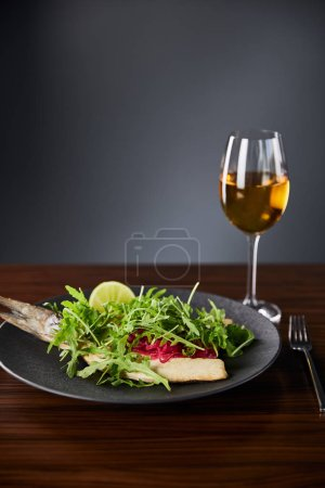 Photo for Tasty restaurant fish steak with lime and arugula on wooden table near fork and white wine on black background - Royalty Free Image