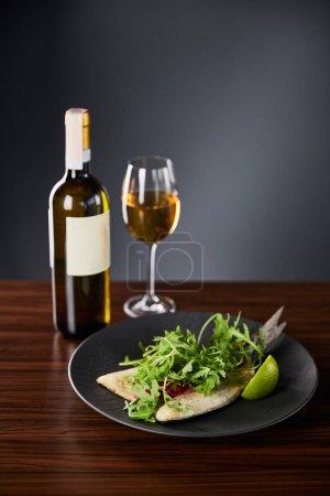 leckeres Restaurant Fischsteak mit Limette und Rucola auf Holztisch in der Nähe von Weißwein auf schwarzem Hintergrund