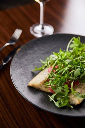 Photo pour Choix sélectif de délicieux steak de poisson avec chaux et arugula sur une table en bois près de la coutellerie - image libre de droit
