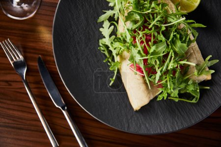 Photo pour Top view of tasty restaurant fish steak with lime and arugula on wooden table near cutlery. - image libre de droit