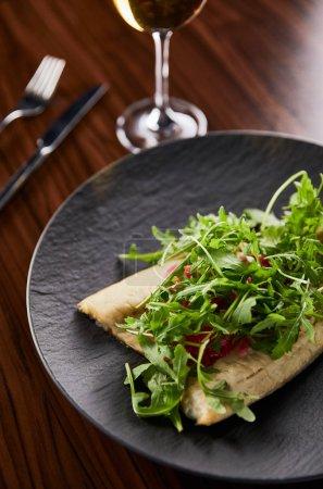 Photo pour Choix sélectif de délicieux steak de poisson avec de la chaux et de l'arugula sur table en bois près de la coutellerie et du vin - image libre de droit