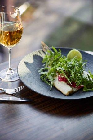 Photo pour Restaurant savoureux steak de poisson avec lime et arugula sur table en bois près de la coutellerie et vin blanc au soleil - image libre de droit