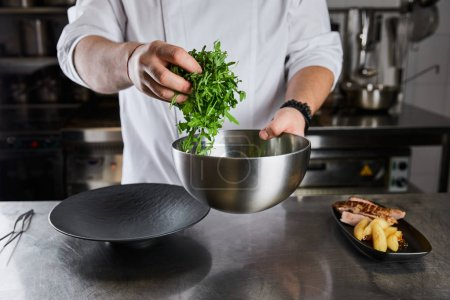 cropped view of chef cooking dish with arugula, meat and potato at kitchen in restaurant