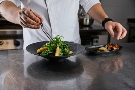 Photo for Partial view of chef cooking dish with arugula, meat and potato at kitchen in restaurant - Royalty Free Image
