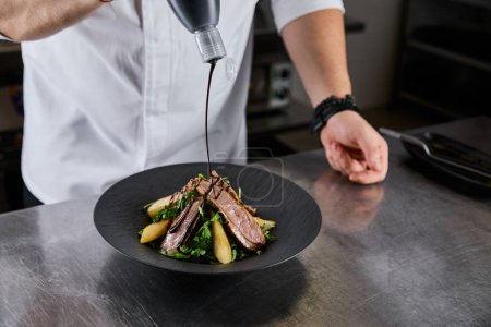 Photo pour Vue partielle du chef versant de la sauce sur un plat avec arugula, viande et pomme de terre dans la cuisine du restaurant - image libre de droit