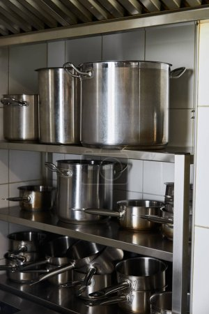 Photo for Metal pots on rack at kitchen in restaurant - Royalty Free Image