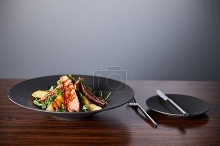 Photo pour Délicieuse salade chaude avec arugula, pomme de terre et viande en assiette noire sur table en bois près de la coutellerie sur fond gris - image libre de droit