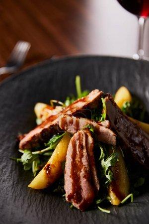 Photo pour Vue de près d'une délicieuse salade chaude avec arugula, pomme de terre et viande en assiette noire sur table en bois - image libre de droit