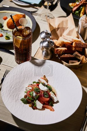 Photo pour Délicieux caviar d'aubergines servi sur table avec cocktail cuba libre au restaurant - image libre de droit
