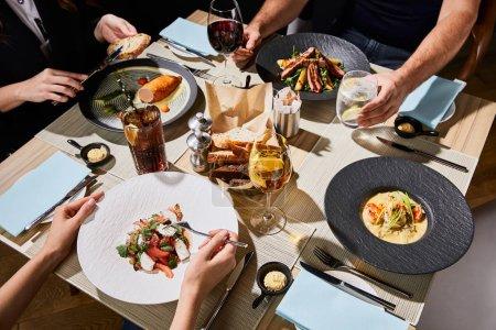 Photo pour Croustillant vue des gens mangeant des aliments délicieux pendant le dîner au restaurant - image libre de droit
