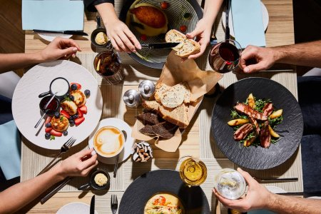 top view of people eating delicious food during dinner in restaurant