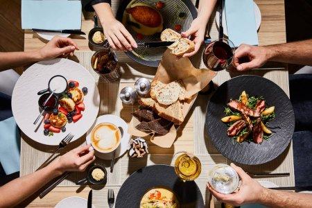 Blick von oben auf Menschen, die während des Abendessens im Restaurant leckeres Essen essen