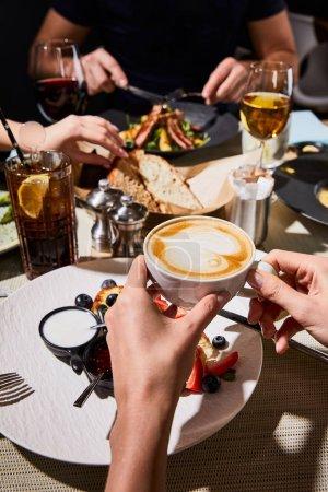 Photo pour Crochet vue d'une femme qui mange du sirniki délicieux et boit du cappuccino pendant le dîner avec des amis au restaurant - image libre de droit