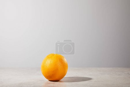 whole and ripe orange on grey background with copy space