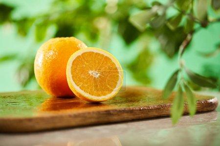 Photo pour Mise au point sélective d'oranges coupées et entières sur planche à découper en bois - image libre de droit