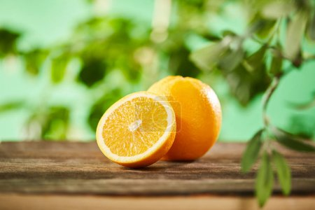 Photo for Selective focus of cut and whole oranges on wooden surface - Royalty Free Image
