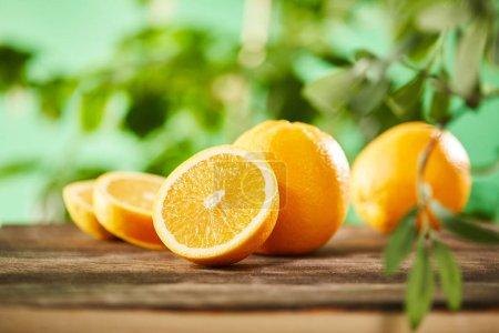 Photo pour Focalisation sélective des oranges coupées et entières sur la surface en bois - image libre de droit