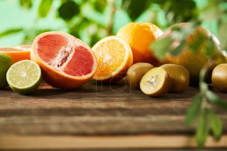 Photo for Selective focus of kiwi, oranges, lime, grapefruit and mango on wooden table - Royalty Free Image