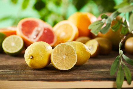 Photo for Selective focus of cut and whole lemons on wooden surface - Royalty Free Image