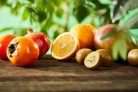 Photo for Selective focus of kiwi, oranges, pomegranate, mango and persimmons on wooden table - Royalty Free Image