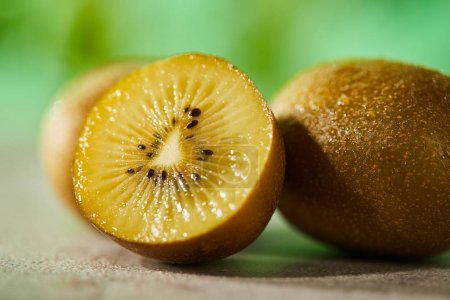 Photo for Close up view of cut and whole kiwi on marble surface - Royalty Free Image