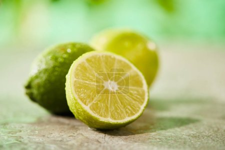 selective focus of whole and cut limes with drops on marble surface