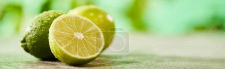 Photo pour Plan panoramique de limes entières et coupées avec des gouttes sur la surface du marbre - image libre de droit