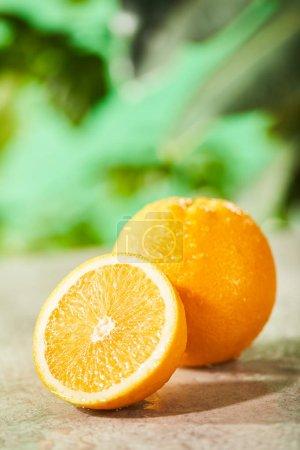Photo pour Foyer sélectif des oranges coupées et entières avec des gouttes sur la surface du marbre - image libre de droit